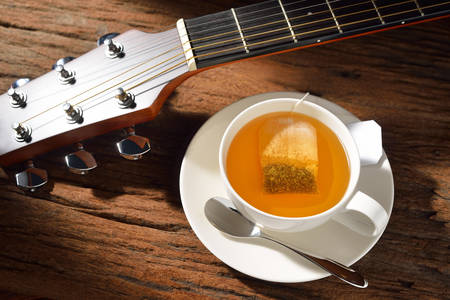 Cup of tea with tea bag and guitar on wooden table photo