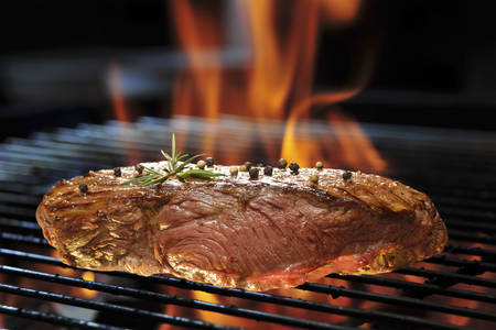 Grilled beef steak on the flaming grill photo