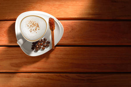 A cup of cappuccino and coffee beans on old wooden background photo