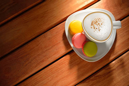 A cup of cappuccino coffee and pastries on old wooden table Banco de Imagens
