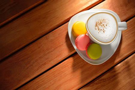 Een kopje cappuccino koffie en gebak op oude houten tafel Stockfoto