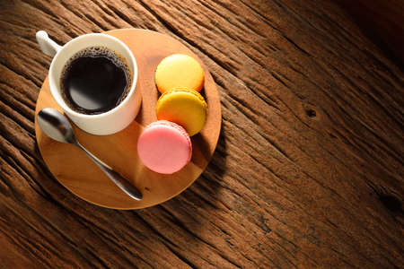 A cup of coffee and pastries on old wooden table photo
