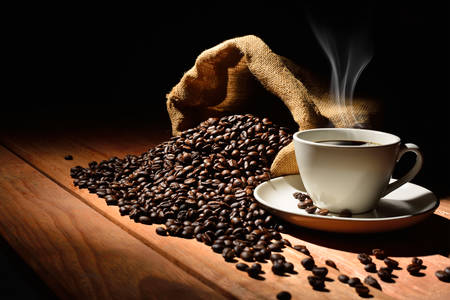 Coffee cup and coffee beans on old wooden table photo