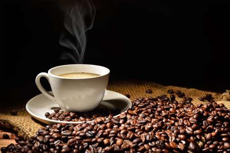Kopje koffie en koffie bonen met rook op jutezak Stockfoto