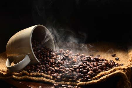 granos de cafe: Granos de café con humo en la taza de café