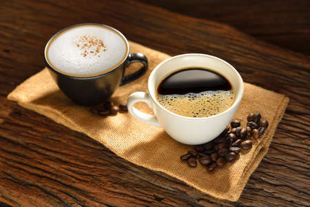 bönor: Kopp kaffe och kaffebönor på säckväv säck Stockfoto
