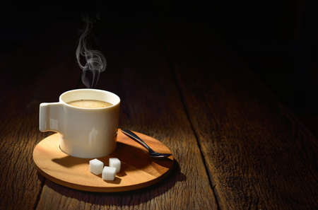 Cup of coffee with smoke and sugar cube on old wooden background photo