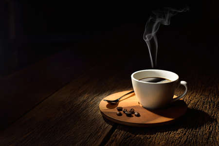 Cup of coffee with smoke and coffee beans on old wooden background Banco de Imagens