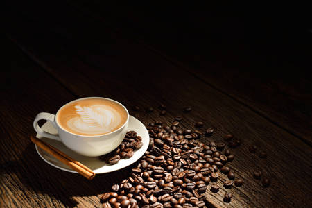 Cup of cafe latte and coffee beans on old wooden background