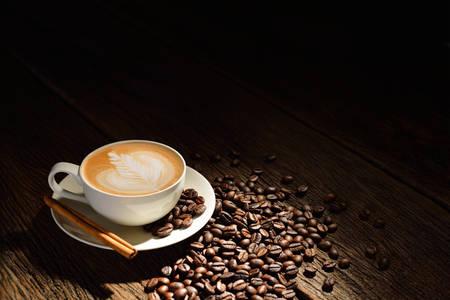 Tasse Café Latte und Kaffeebohnen auf alten hölzernen Hintergrund Lizenzfreie Bilder