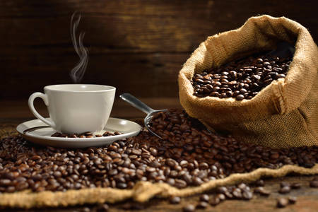 Coffee cup and coffee beans on old wooden table