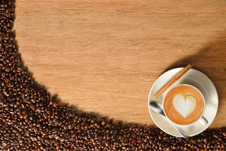 Top view of a cup of coffee and coffee beans on old wooden background