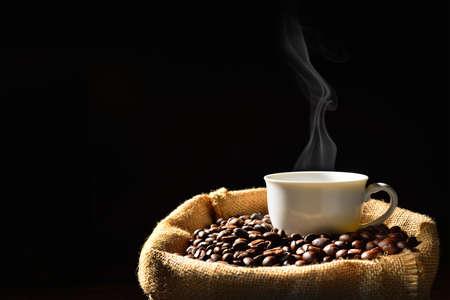 granos de cafe: Taza de café con humo y granos de café en saco de arpillera Foto de archivo