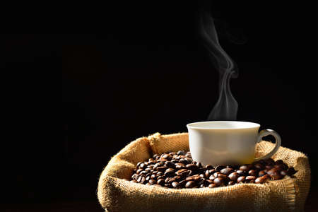 Cup of coffee with smoke and coffee beans in burlap sack