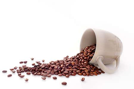 grano de cafe: Granos de café en la taza de café aislados en blanco Foto de archivo