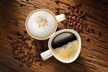 Two cups of coffee and coffee beans on old wooden table Stockfoto