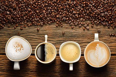 bönor: Olika koppar kaffe och kaffebönor på gamla träbord