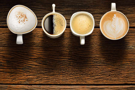 Variety of cups of coffee on old wooden table photo