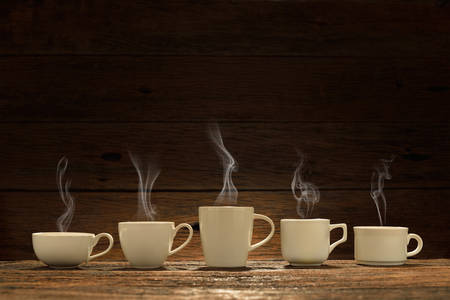 Variety of cups of coffee with smoke on wooden background