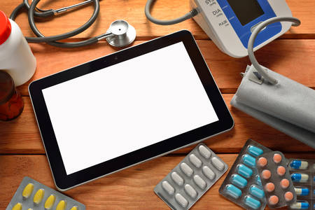 Tablet pc computer with medicines, stethoscope and automatic blood pressure photo