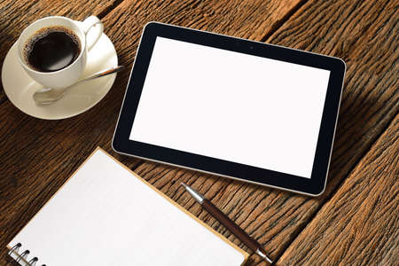 Tablet computer with notepad and coffee cup on old wooden background photo