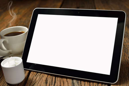 Tablet computer and coffee cup on old wooden background photo