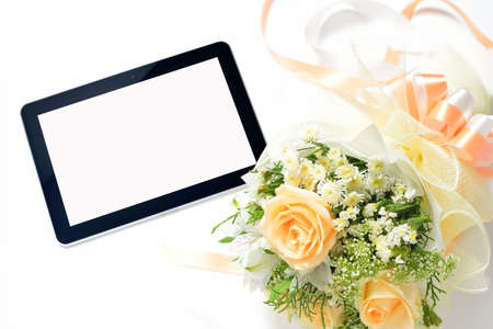 Tablet computer and bouquet of flowers isolated on white photo