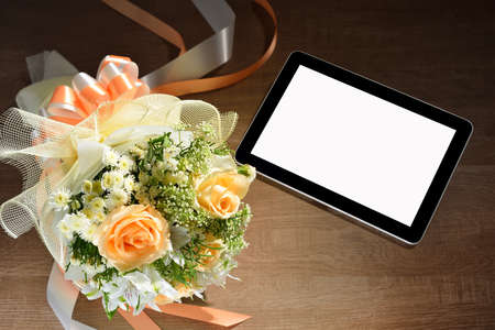 Tablet computer and bouquet of flowers on wooden background photo