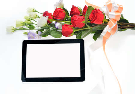 Tablet computer and beautiful bouquet of flowers isolated on white photo