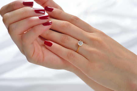 Wedding ring on hand of bride on white cloth Banco de Imagens