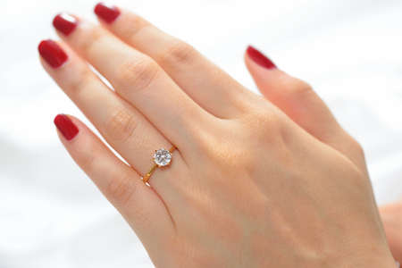 Wedding ring on hand of bride on white cloth photo