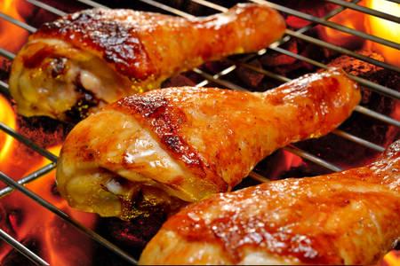 Gegrillte Hühnerbeine auf dem flammenden Grill Standard-Bild