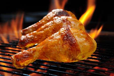 Gegrilde kip benen op de vlammende grill