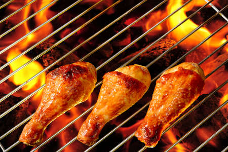 chicken grill: Grilled chicken legs on the flaming grill Stock Photo