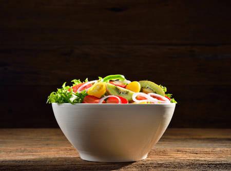ensalada de verduras: Frutas y verduras ensalada en un taz�n en mesa de madera