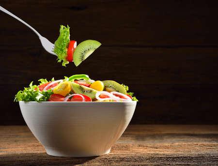 ensalada de verduras: Frutas y ensalada de verduras en un bol y recogido por un tenedor sobre fondo de madera