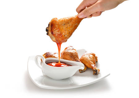 Hand holding grilled chicken leg dipping in ketchup photo