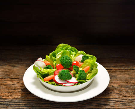 Fruit and vegetable salad in a bowl on wooden table photo