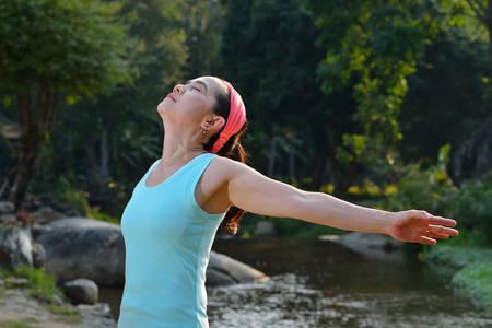 persona respirando: Mujer que estira sus brazos para disfrutar del aire fresco en el parque Foto de archivo
