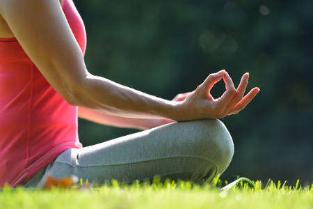 Middle aged woman practicing yoga meditation outdoor