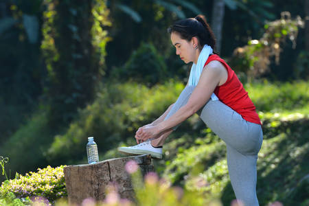 shoelace: Middle aged woman exercising in the park