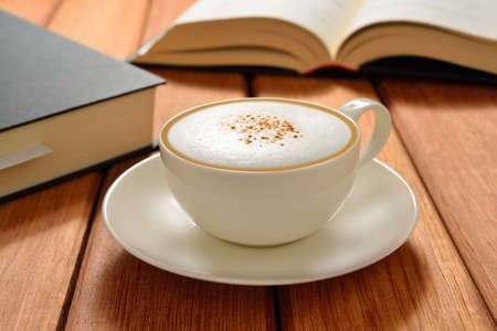 cappuccino: Cup of cappuccino coffee and books on wooden table