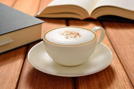 capuchino: Taza de café capuchino y libros sobre la mesa de madera Foto de archivo