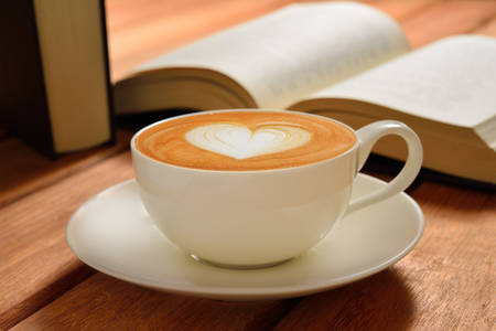 cafe latte: A cup of cafe latte and books on wooden table