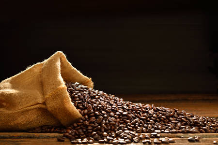 granos de cafe: Granos de caf� en saco de arpillera en mesa de madera, Esta foto est� disponible con el humo