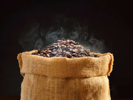 Coffee beans with smoke in burlap sack