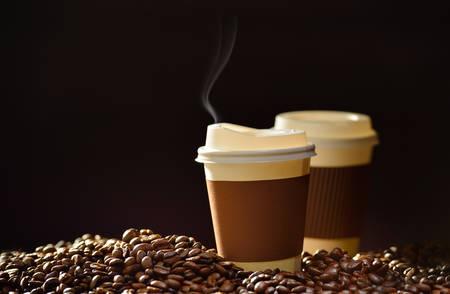frijoles: Taza de papel de caf� y granos de caf� en la mesa de madera