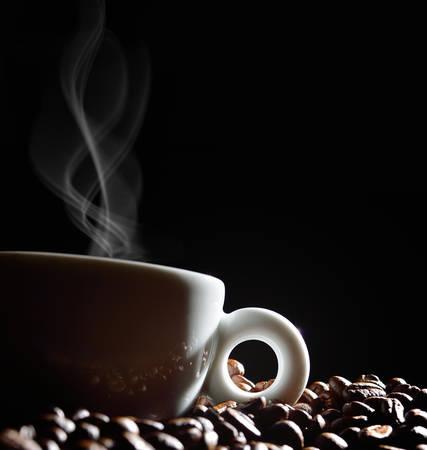 Kopje koffie met rook en koffie bonen op zwarte achtergrond