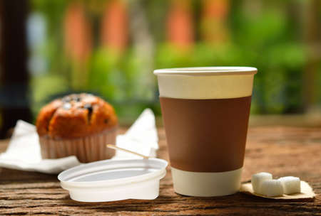 to go cup: Paper cup of coffee and cake on wooden background Stock Photo
