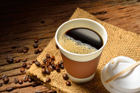 caliente: Taza de papel de café y granos de café en la mesa de madera